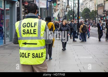 Käufer übergeben Mann trägt Warnschutz-Jacke mit Golf Verkauf Werbeschild. Oxford Street, London - Stockfoto