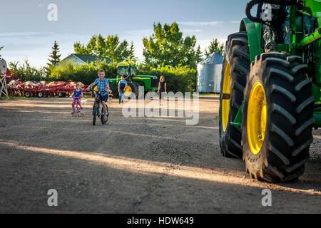 Kinder Fahrrad neben einem großen Traktor auf dem elterlichen Hof wie die Eltern stehen gerade im Hintergrund; Herschel, - Stockfoto