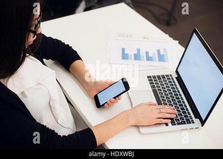 Junge Frau mit einem Telefon. Arbeitsplatz in der Nähe der Fenster mit Laptop. Nahaufnahme - Stockfoto