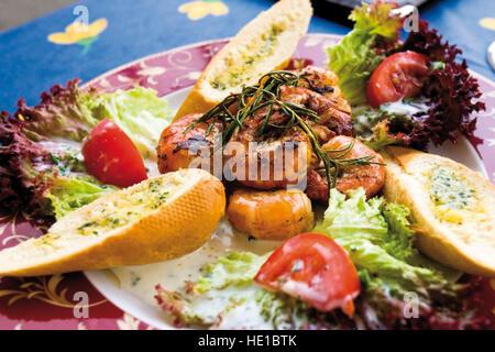 Gebratene Riesengarnelen und Brot mit Kräuterbutter - Stockfoto