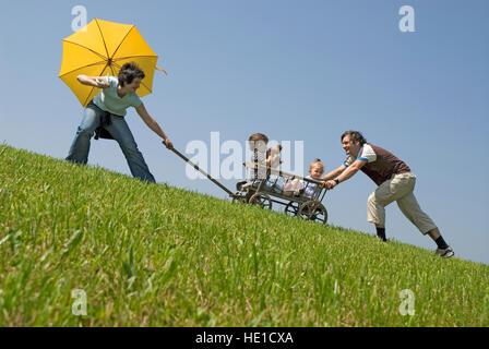 Familie, paar ziehen und schieben ihre Kinder auf einem Wagen, Spielzeug Wagen - Stockfoto