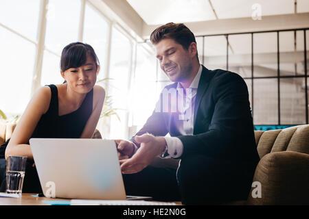 Aufnahme von zwei jungen Geschäftsleuten mit Laptop in der Lobby des modernen Büros. Mann und Frau sitzen im Foyer - Stockfoto