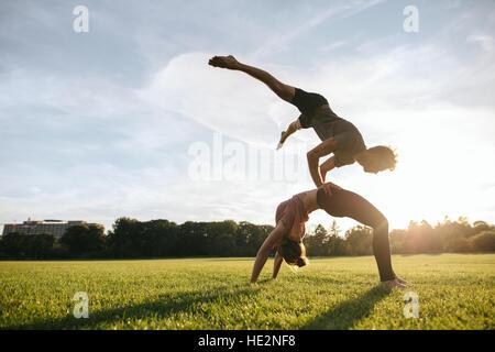 Gesunde junge Paar paar Yoga im Freien im Park machen. Mann tut Handstand am Oberkörper der Frau im Park. - Stockfoto