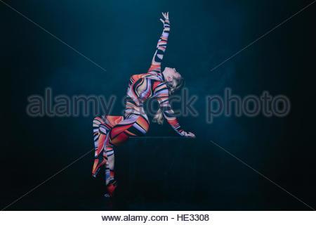Junge flexible blonde Zirkus Acrobat posiert im Studio in Tracht. Equilibre Gleichgewicht Handstand auf einem Cube - Stockfoto