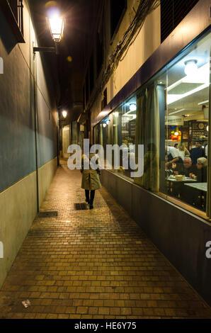 Frau kommt in niedrigen hellen, schmalen dunklen Gasse. Bar daneben. Spanien - Stockfoto