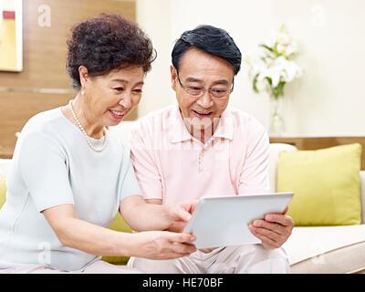 hochrangige asiatische paar sitzt auf couch Blick auf Tablet-Computer zusammen, glücklich und lächelnd - Stockfoto