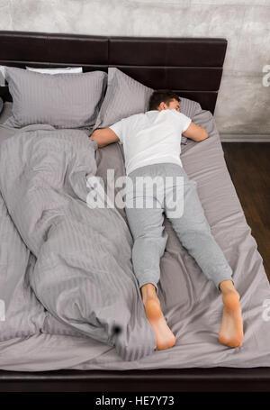 h bscher m de mann im pyjama schlafen alleine ohne decke und eine kissen in stilvolles bett in. Black Bedroom Furniture Sets. Home Design Ideas