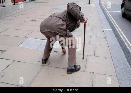 Älterer Mann verwendet Gehstock für Unterstützung, da er biegt um ein Element aus dem Bürgersteig abholen - Stockfoto