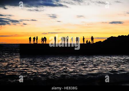 Menschen-Silhouetten auf dem Meer Pier bei Sonnenuntergang. Kanarische Insel Teneriffa. Spanien - Stockfoto