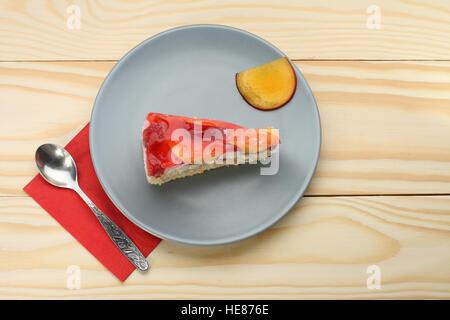 Erdbeere und Pfirsich-Kuchen mit Gelatine auf graue Platte auf Holztisch - Stockfoto