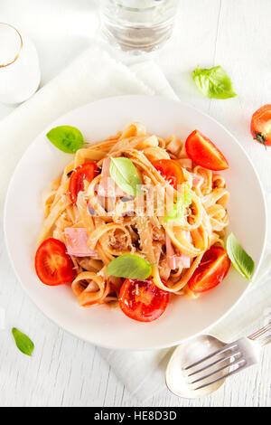 Tagliatelle-Nudeln mit Schinken, Tomaten-Sauce, Cherry-Tomaten und Basilikum Blätter auf weißen Teller - hausgemachte - Stockfoto