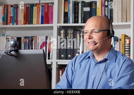 Lächelnder senior Mann mit Kopfhörer, Computer und Webcam im Gespräch mit seiner Familie über das Internet, Bücher - Stockfoto