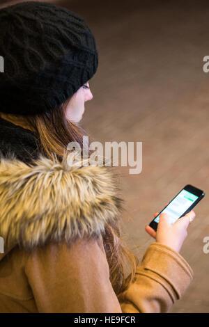 Frau SMS auf smart Phone in der Nacht im winter - Stockfoto