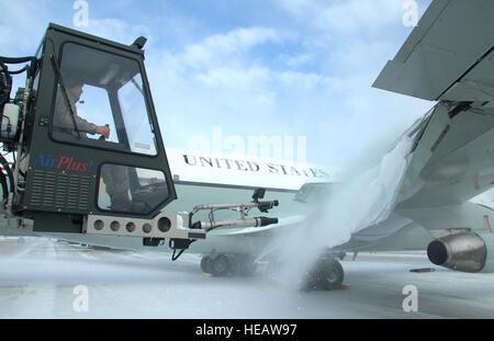 US Air Force Senior Airman Kyle Kindig betreibt eine Luft-Kanone von einem Enteisung LKW zum Schlag Schnee vom Flügel - Stockfoto