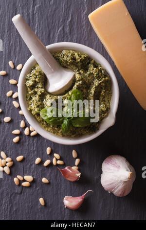 Italienische grüne Pesto-Sauce in einem Mörser und Zutaten Nahaufnahme auf dem Tisch. vertikale Ansicht von oben - Stockfoto