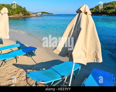 Sommer morgen sandigen Ksamil Strand mit liegen und Sonnenschirmen (Albanien). - Stockfoto