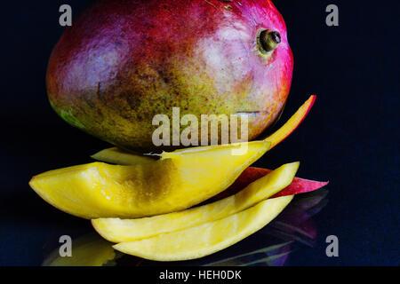Geschnittene Mango mit Biss genommen.  Schwarzer Hintergrund. - Stockfoto