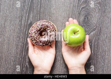 Gesunden Lebensstil oder Ernährung Konzept mit jungen Frau, die in den Händen halten, einen grünen Apfel und einen - Stockfoto