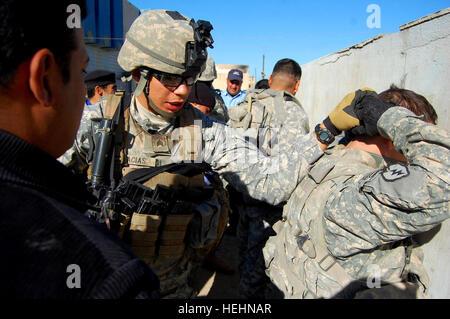 Sgt. Tony Macias, Wauchula, Florida, zeigt eine irakische Polizisten die richtige Art und Weise die Kontrolle über - Stockfoto