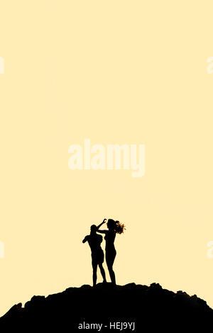 Mann und Frau stehen auf Bergsilhouette mit Textfreiraum - Stockfoto