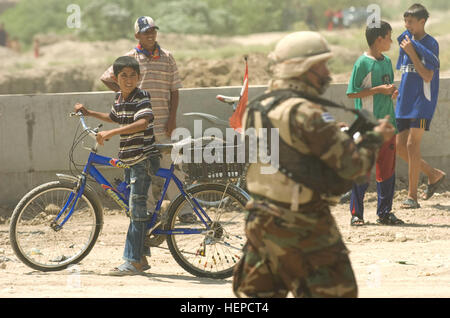 Ein Junge hält über eine neu gebaute Kanalbrücke in Numaniyah, Irak, ein Soldat der El Salvador-Bataillon-Cuscatlan - Stockfoto