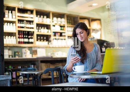 Junge Frau lesen Smartphone Texte im café - Stockfoto