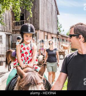 Vater guiding Tochter Reitpferd - Stockfoto