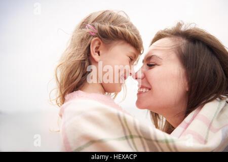 Glückliche Mutter und Tochter in Decke gehüllt, Nasen reiben - Stockfoto