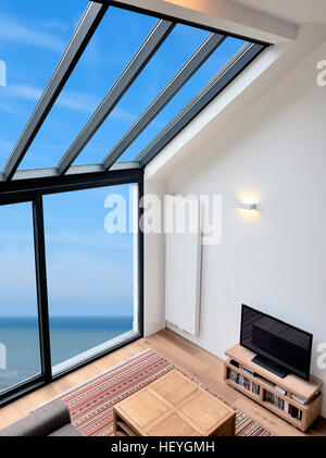 Modernes Wohnzimmer mit großen Fenstern und Blick auf Meer. Ansicht von oben - Stockfoto