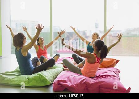 Frauen mit Kissen in Übung Klasse Gym Studio erhobenen Armen gelehnt - Stockfoto