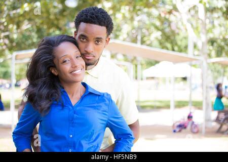 Closeup Portrait eines jungen Paares, Mann im gelben Hemd Holding Frau mit blauen Shirt von hinten, glückliche Momente, - Stockfoto