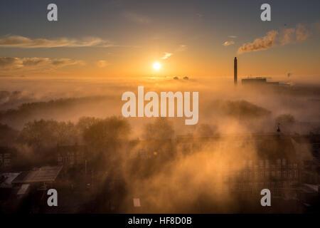 London, UK. 28. Dezember 2016. UK Wetter: Nebel und eine dramatische Sonne geht über Deptford Park in SE London - Stockfoto
