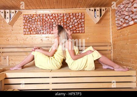 Schöne junge Freundinnen kommen zusammen, um Entspannung im Spa zu verwenden. Ein entspannendes Saunabad. - Stockfoto