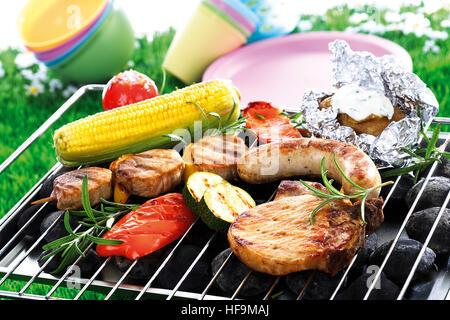 Grill-Szene: gebratene Wurst, Filet Spieß, Kotelett, Kartoffeln eingewickelt in Alufolie mit Dip, Maiskolben, Paprika - Stockfoto