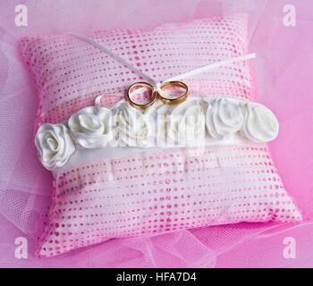 Doppel Gold Ringe auf einem Rosa kissen mit weißen Rosen gebunden - Stockfoto