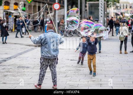 Jungen spielen mit riesigen Seifenblasen in den Straßen von Spanien glückliches Lächeln Jump run Spiel - Stockfoto
