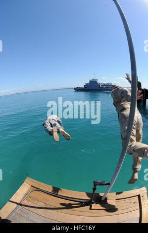 Army Staff Sgt Benjamin Cossel links (), ein Soldat nach vorn für Joint Task Force Guantanamo, Sprünge an der Pier - Stockfoto