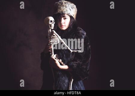 Fantasy Horror und Halloween: eine schlanke zierliche junge Olive enthäuteten Woman Mädchen trägt eine alte schwarze - Stockfoto