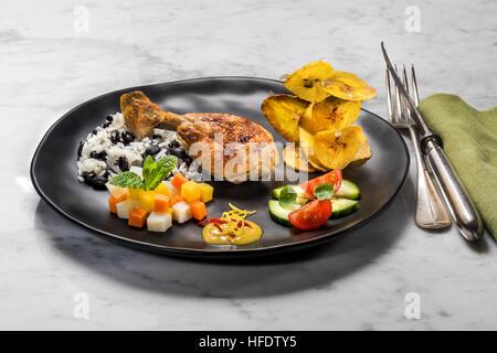 Typische kubanische Speisen, Huhn, Reis mit schwarzen Bohnen, gebratene Bananenchips, Salat und Gemüse. KUBA. Kuba - Stockfoto
