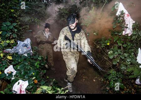Gruppen von Menschen verkleidet in Bekämpfung Tarnung Uniformen und tragenden Paintball Waffen Jagd Zombies im Wald - Stockfoto