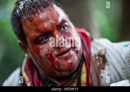 """Ein Mann gekleidet und geschminkt mit ein blutiges Gesicht wie ein Zombie in den Wäldern in einem """"The Walking Dead - Stockfoto"""