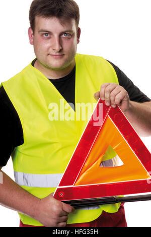 Bauarbeiter tragen eine gelbe Warnweste hält ein Vorsicht-Dreieck - Stockfoto