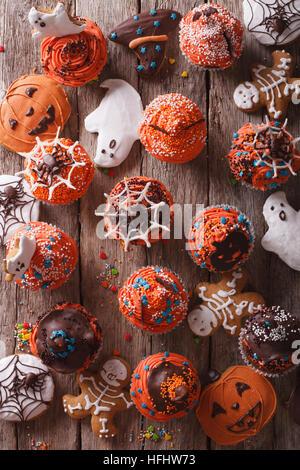 Halloween Cupcakes und Lebkuchen auf dem Tisch. vertikale Ansicht von oben - Stockfoto