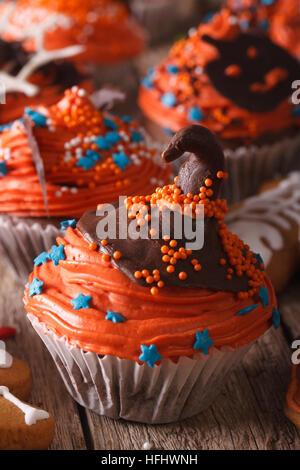 Festliche Halloween Cupcakes mit Schokolade Hexen Hut close-up auf dem Tisch. Vertikal - Stockfoto