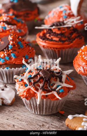 Schöne orange Halloween Cupcakes mit Spinne Nahaufnahme auf dem Tisch. vertikale - Stockfoto