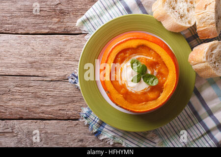Pürieren Sie Suppe mit saurer Sahne und Basilikum in einer gebackenen Kürbis. horizontale Ansicht von oben - Stockfoto