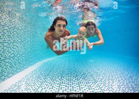 Familie Fitness - Mutter, Vater, Sohn lernen, gemeinsam schwimmen, Tauchen unter Wasser im Schwimmbad aktive Eltern - Stockfoto