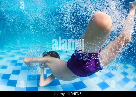 Lustige Porträt des Kindes schwimmen und Tauchen im blauen Pool mit Spaß - springen unter Wasser mit Spritzern und - Stockfoto