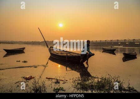 Ein Ruderer sitzt auf seinem verankerte Holzboot bei Sonnenuntergang am Fluss Damodar nahe Durgapur Barrage, West Bengal, Indien.