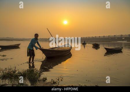 Ruderer versucht, sein Boot ans Ufer bei Sonnenuntergang am Fluss Damodar nahe Durgapur Barrage, Westbengalen, Indien - Stockfoto